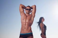 摆在海滩的运动的人 免版税库存图片
