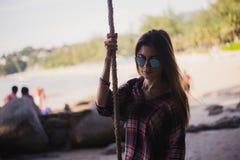 摆在海滩的逗人喜爱的女孩 她举行一条绳索和很远看 时尚商店的完善的照片 免版税库存照片