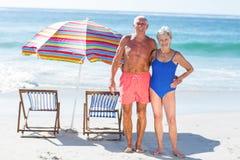 摆在海滩的逗人喜爱的成熟夫妇 免版税库存图片