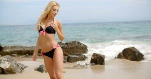 摆在海滩的黑比基尼泳装的白肤金发的妇女 股票视频