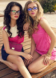 摆在海滩的玻璃的美丽的性感的女孩 免版税库存照片