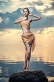 摆在海滩的年轻美丽的妇女在日落 免版税库存图片