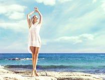 摆在海滩a的白色比基尼泳装的美丽,适合和性感的女孩 免版税库存照片