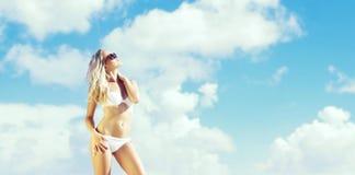 摆在海滩a的白色比基尼泳装的美丽,适合和性感的女孩 图库摄影