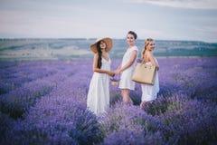 摆在淡紫色领域的三名妇女 库存图片