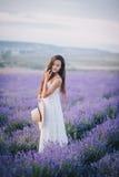 摆在淡紫色领域的美丽的少妇 免版税库存图片