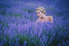 摆在淡紫色领域的美丽的少妇 图库摄影