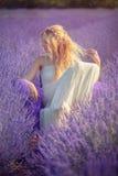 摆在淡紫色领域的美丽的少妇 库存图片