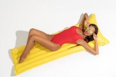 摆在游泳床垫的性感的女孩在被隔绝的太阳下 库存图片