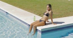 摆在游泳池边的可爱的妇女 免版税图库摄影