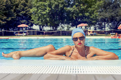 摆在游泳池边的泳装的迷人的夫人 免版税图库摄影