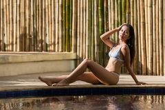摆在游泳池附近的亚裔妇女 图库摄影