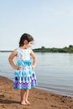 摆在湖背景的巧妙的礼服的小女孩 免版税库存照片