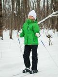 摆在滑雪的高尔夫球外套和白色帽子的女孩在冬天森林 免版税库存图片