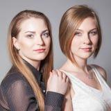 摆在演播室的两个美丽的女朋友 免版税库存照片