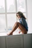 摆在演播室的性感的年轻正面妇女画象在自然光,佩带的蓝色衬衣,有好和健康适合 免版税库存图片