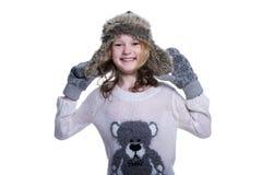 摆在演播室的愉快的逗人喜爱的孩子隔绝在白色背景 佩带的冬天衣裳 被编织的羊毛毛线衣,围巾,帽子 免版税图库摄影