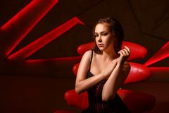 摆在演播室的红色椅子的美丽的妇女 库存图片