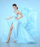 摆在演播室的蓝色礼服的美丽的高档时尚妇女 在吹薄绸的礼服的魅力模型 惊人的妇女 库存图片
