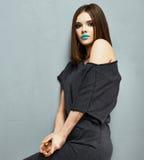 摆在演播室的黑礼服时装模特儿 免版税库存图片