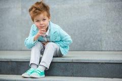 摆在灰色墙壁附近的时尚孩子 免版税图库摄影
