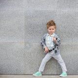摆在灰色墙壁附近的时尚孩子 库存照片