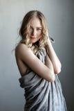 摆在灰色墙壁附近的年轻性感的妇女画象  图库摄影
