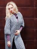 摆在灰色的惊人的白肤金发的女孩编织了在街道上的外套在生锈的金属墙壁背景  方式 beauvoir 免版税库存照片