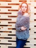 摆在灰色的惊人的长发白肤金发的女孩编织了毛线衣和牛仔裤在街道在木墙壁背景  免版税库存图片