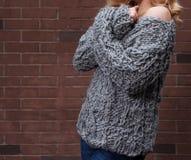 摆在灰色的惊人的长发白肤金发的女孩编织了毛线衣和牛仔裤在街道在砖墙背景  免版税库存照片