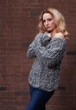 摆在灰色的惊人的长发白肤金发的女孩编织了毛线衣和牛仔裤在街道在砖墙背景  免版税库存图片
