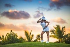 摆在热带手段蓬塔Cana的高尔夫球法院的女孩 库存图片