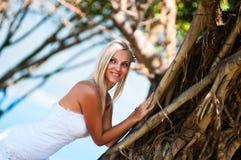 摆在热带树中间的性感的新娘 免版税库存图片