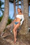 摆在热带海滩的妇女在棕榈附近 免版税库存照片