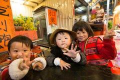 摆在照相机前面的台湾土产兄弟姐妹 免版税库存图片