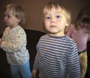 摆在照相机前面的小逗人喜爱的白肤金发的男孩 免版税库存图片
