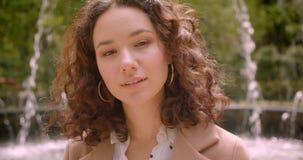 摆在照相机前面的年轻快乐的俏丽的长发卷曲白种人女性特写镜头画象户外  股票录像