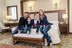 摆在照相机的一个愉快的家庭在旅馆客房坐床 库存照片