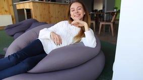 摆在照相机的可爱的女学生画象,坐在时髦的咖啡馆的软的椅子在秋天下午 影视素材