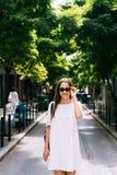 摆在照相机的可爱的妇女 太阳镜的一个女孩旅行 库存照片