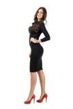 摆在照相机的短的黑礼服的年轻拉丁美州的女商人 库存图片