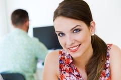 摆在照相机的美丽的女实业家在办公室 免版税库存图片