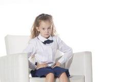 摆在照相机的逗人喜爱的小女孩 坐在一把白色椅子的滑稽的孩子 背景查出的白色 可爱的学校 免版税库存图片