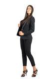 摆在照相机的黑衣服的严肃的坚强的性感的女商人 免版税库存图片