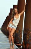 摆在牛仔裤短裤的美丽的性感的妇女 免版税库存图片