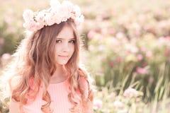 摆在玫瑰园里的十几岁的女孩 免版税图库摄影