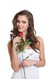 摆在玫瑰年轻人的美丽的女孩 免版税库存图片