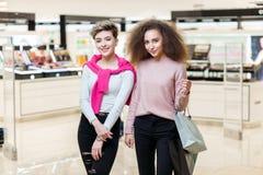 摆在现代购物中心背景的两个最好的朋友同事女孩 免版税库存照片