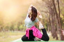 摆在瑜伽asana的妇女在自然庭院 免版税库存图片