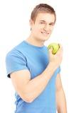 摆在用一个绿色苹果的英俊的年轻人在他的手上 库存照片